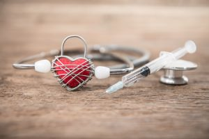27342563 - red heart and a stethoscope on wood background