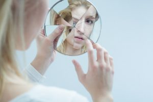 55659743 - young woman touching her own reflection in a broken mirror