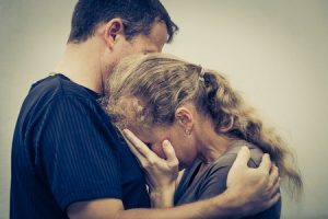 32429439 - sad woman hugging her husband