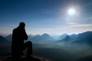 57570588 - photographer takes photos with mirror camera on peak of rock. dreamy landscape, orange sun at horizon